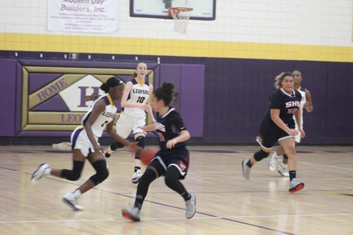 SHS #11 Samantha Suarez puts some pressure on HHS #0 Sy Crowley as she dribbles up the court.