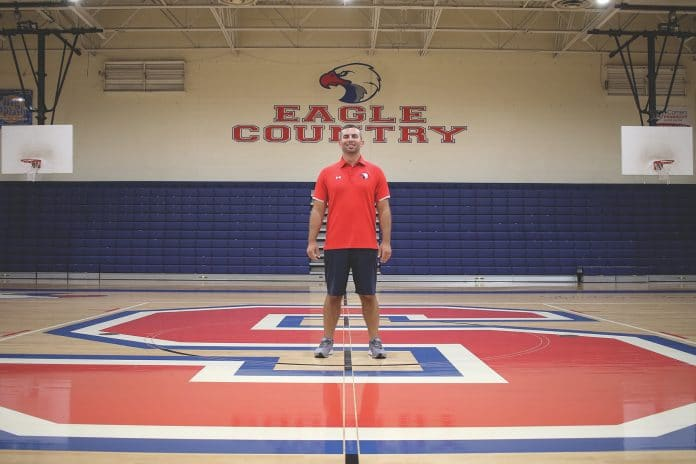 Springstead High AD Dustin Kupcik stands center court in the SHS gym. Over two years, the gym has seen some changes, from new lights to graphics. Photo by Alice Herden.
