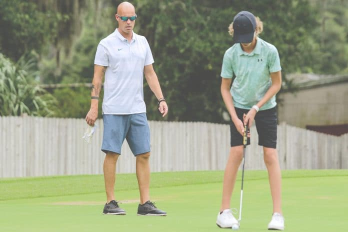 Leopards golf coach Kevin Bittinger watches his son and Leopards golfer Drew Bittinger attempt a put during their practice on August 16 at Brooksville Country Club in Brooksville.
