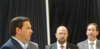 Governor DeSantis addresses the press in Hudson last month and announces the opening of the monoclonal antibody treatment center there.  Background (L-R) Kevin Guthrie, Dr. Kenneth Scheppke. Photo by Sarah Nachin.